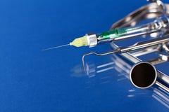 Outils de dentiste sur un bleu Image stock