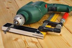 Outils de foret électrique et de menuiserie sur un plancher en bois Image libre de droits