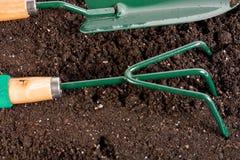 outils de jardinage dans le sol composté par noir Photos stock
