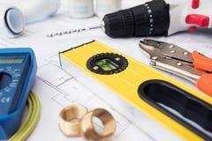 Outils et composants de bâtiment disposés sur des plans de Chambre photo stock