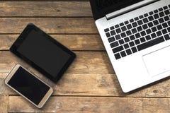 Outils modernes de communication électronique sur un plancher en bois photo stock