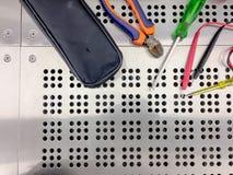 Outils pour des électriciens sur la terre arrière de feuillard, technicien d'équipement photo stock