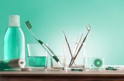 Outils pour l'hygiène buccale sur la table en bois avec le fond vert images libres de droits