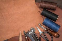 Outils pour l'ouvrage de cuir et les morceaux de cuir brun Photo stock