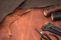 Outils pour l'ouvrage de cuir et les morceaux de cuir brun Fabrication de cuir Photo stock
