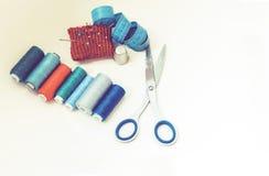 Outils pour la couture, la protection tricotée rouge d'aiguille pour coudre, les ciseaux et les bobines colorées de fil sur le fo image stock