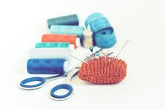 Outils pour la couture, la protection tricot?e rouge d'aiguille pour coudre, les ciseaux et les bobines color?es de fil sur le fo image libre de droits