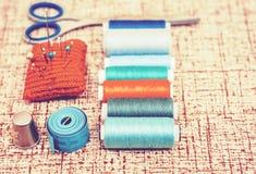 Outils pour la couture, la protection tricot?e rouge d'aiguille pour coudre, les ciseaux et les bobines color?es de fil sur le fo photos libres de droits