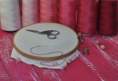 Outils pour le fil de couture et tons rouges sur une table en bois Photos stock