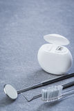 Outils, soie et brosse dentaires de base sur la surface grise Images libres de droits