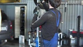 Outils sur la boîte et le mécanicien avec le marteau réparant l'automobile Inclinaison  banque de vidéos