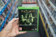 Outlast Trinity videogame on XBOX One. Bratislava, Slovakia, circa april 2017: Man holding Outlast Trinity videogame on Microsoft XBOX One console in store Stock Images