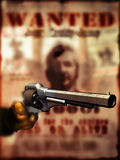 Outlaws. Close view on a gloved hand holding a gun Remington 1858 model, at the foreground of a blurry reward announcement Royalty Free Stock Images