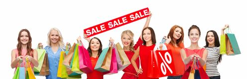 Happy women with shopping bags and sale sign royalty free stock images