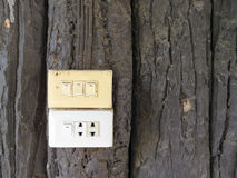 Outlet and switch on the background of wooden wall Royalty Free Stock Photography
