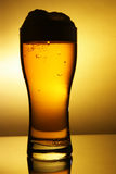 Outline of beer glass. With froth over yellow background royalty free stock photography