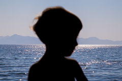 Outline of the child on the background of the sea lit by the setting sun Stock Photo