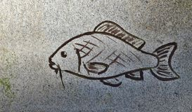 The outline of a fish carved in stone