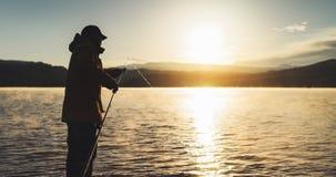 Outline fisherman fishing rod at sunrise sunlight, man enjoy hobby on evening lake, person catch fish on background night