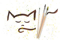 Outline gouache sketch of cat face and three paint brushes on a background with sprays. Outline gouache sketch of cute cat face and three used paint brushes on a royalty free illustration