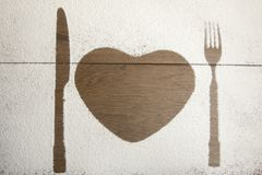 Heart outline with knife and fork. Outline of heart with knife and fork on wooden boards with copy space royalty free stock photo