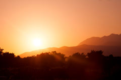 Outline photo of sun setting over mountains Royalty Free Stock Images