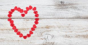 Outline of red heart shapes on rustic white wood background. Outline of red heart shapes on rustic white wood in flat lay view stock photo