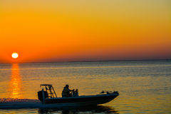 The outline of a speeding boat at sunrise on Tampa Bay, Floridal Stock Photos