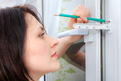 She outlines the stopper attachment points on PVC windows. Stock Images