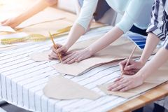 Outlining a new fashionable pattern. Start working. Three attentive tailors outlining the sewing pattern of a fashionable summer dress Royalty Free Stock Image