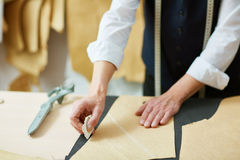Outlining paper pattern. Hands of tailor outlining paper pattern Stock Images