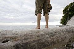 The outlook. Man standing barefoot on a big driftwood tree trunk watching the ocean on the island of ruegen, germany stock photo