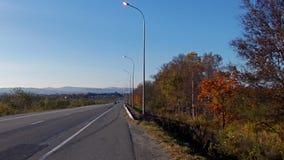 outono atrasado, estrada na distância, montanhas azuis e céu azul fotos de stock royalty free