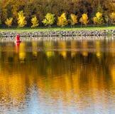 Outono colorido Aleia ao longo do riverbank no fundo do parque do outono Reflexões no rio imagem de stock