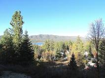 outono, 2017 no lago big Bear, Califórnia: floresta no primeiro plano com parte do lago & das montanhas de Big Bear vistos no fun fotos de stock royalty free