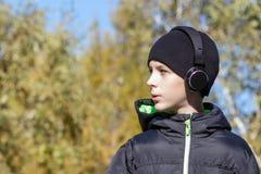 outono Um menino em fones de ouvido pretos, em um revestimento preto e em vestir um chapéu olha a esquerda imagem de stock royalty free