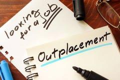 Outplacement som är skriftlig på en notepad Arkivfoto