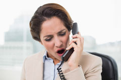 Outraged businesswoman shouting into phone Royalty Free Stock Image