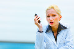Outraged modern business woman with cell phone Royalty Free Stock Image