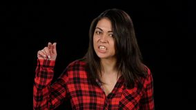 Outraged woman shouts and something to prove. Black. Close-up. Irritable woman shouts, outraged and something to prove. Female in a plaid red shirt with long stock footage
