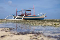 Outrigger boat on the beach during low tide stock photos