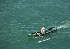 Outrigger Canoe. A man in an outrigger canoe in the waters around the island of Bali, Indonesia Royalty Free Stock Photo