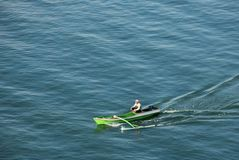 Outrigger Canoe. Man in an outrigger canoe in the waters around the island of Bali, Indonesia Royalty Free Stock Photos