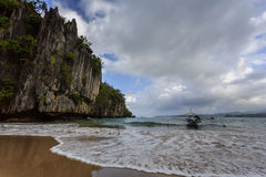 Outrigger canoe moored at beach near over hanging cliffs in Philippines Royalty Free Stock Photography