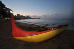 An outrigger canoe sits on the beach Royalty Free Stock Photos