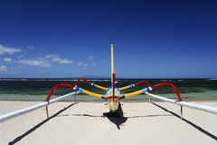 Outrigger Fishing boat sanur beach bali indonesia. Traditional colorful outrigger balinese fishing boat on white sand sanur Candidasa beach, bali, indonesia stock photos
