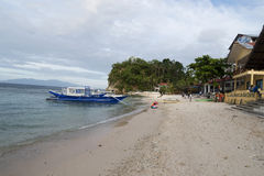 Outrigger next to a small tropical beach in the Philippines Royalty Free Stock Photo