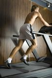 Outrunner. Young man without shirt running on track in gym. Whole body, rear view Royalty Free Stock Photos