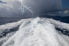 Outrunning the Storm. The wake from a high-speed boat as it heads away from a storm royalty free stock photography