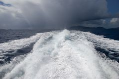 Outrunning the Storm. The wake from a high-speed boat as it heads away from a storm stock images